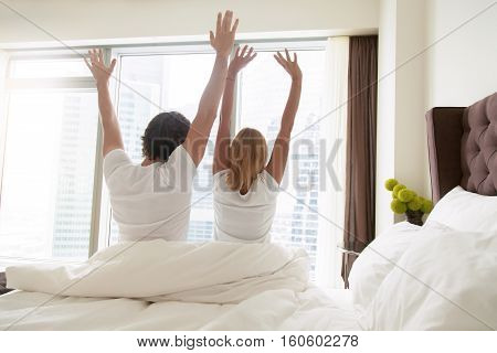 Back view of young happy couple in white t-shirts waking up in the morning, sitting on bed, stretching in cozy bedroom, looking through window at big city scenery. Funny married couple after wakeup