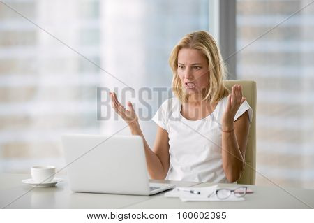 Attractive mad businesswoman in white blouse sitting at her workplace in office, looking at laptop screen with angry expression. Too much workload, file error, all data failed, forgot to save document