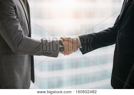 Close up of hands of two business partners making agreement, taking a big deal and shaking hands in meeting room at office. Urban style glass office building in big city on the background. Side view