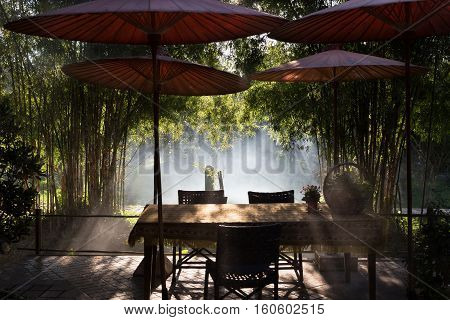 Table And Chair And Red Umbrella At Patio With Light Ray Through Bamboo Tree