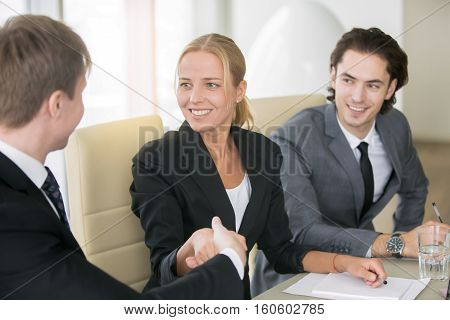 Nice to meet you. Portrait of young confident friendly smiling middle aged businesswoman shaking hands with her business partner or client during meeting, introducing herself, achieving agreement