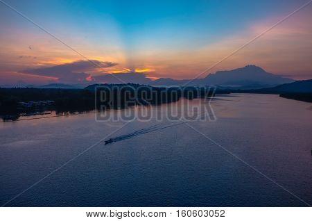 Majestic mountain Kinabalu with beautiful sunrise & ray of light at Mengkabong river,Tuaran,Sabah,Borneo.Nature view of Borneo tropical jungle.
