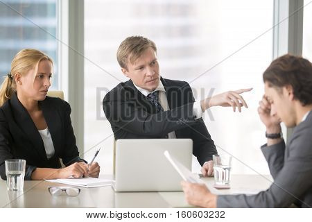 Furious client scolding, firing incompetent contractor after unproductive work results. Young frustrated businessman receiving dismiss notification from his partner for incompetence