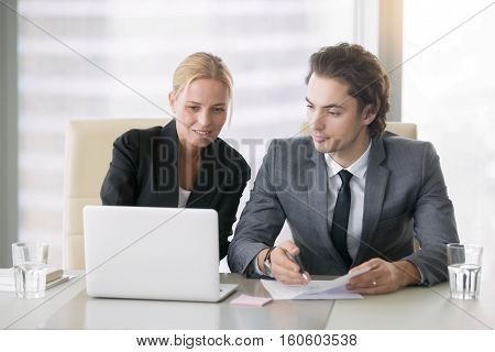 Group of two business partners discussing new project at meeting in office room, using laptop. Mid aged businesswoman and her young associate browsing presentation on screen. Business concept