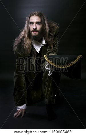 studio photography medieval wary pirate man with long hair and beard sat down on one knee looking away