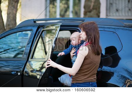Young Mother With Her Baby Getting Into A Car