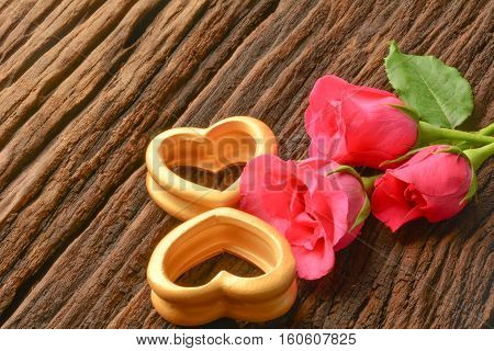 The wood hearts and three pink rose on bark.