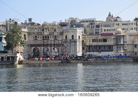 UDAIPUR, RAJASTHAN, INDIA - FEBRUARY 07, 2016 - Buildings and unidentified crowd from lake Pichola