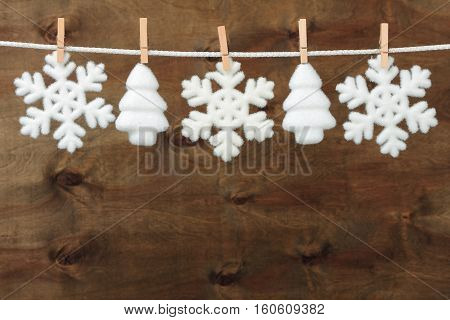 Christmas baubles in shape of snowflake and spruce on brown wooden background