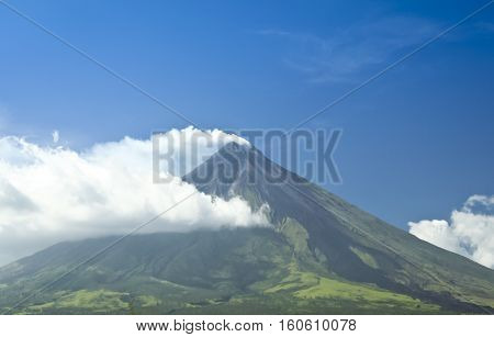 mt mayon volcano smoking against a blue sky with dark trail of lava marking the sides from a recent eruption