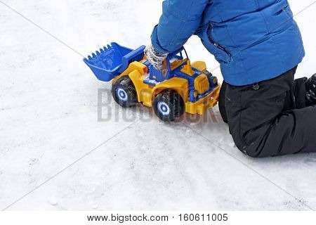 Part of the image of a small child who sits in the snow and plays with a big bright toy car excavator.