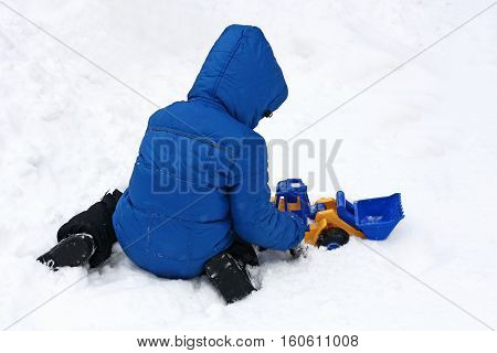 The image of a small child who sits in the snow and plays with a big bright toy car excavator.