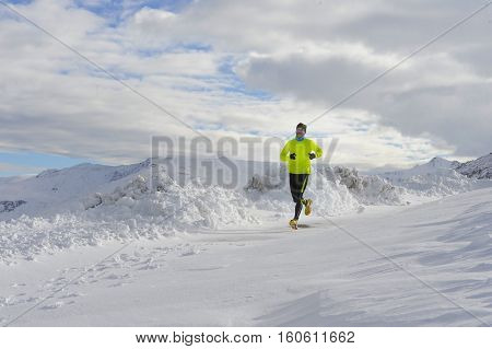 young healthy sport man running in snow mountains in trail runner hard workout in energy and endurance concept with a beautiful cold winter background