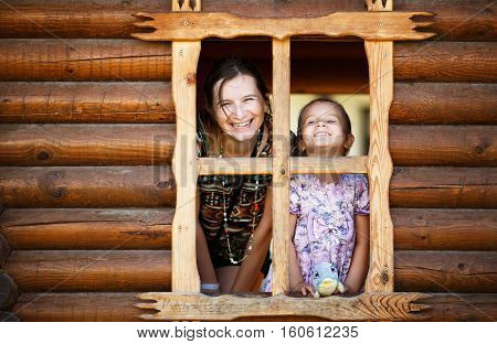 Happy smiling mom and daughter look out of the window a wooden timbered hut. Mother and baby girl looking out the window. Happy family.