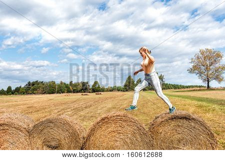 Young woman jumping over hay roll bales in a field