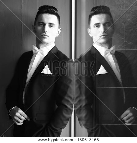 Man in suit with bow tie hand in pocket young elegant stylish turns sideway stands and reflects in mirror black and white on grey background