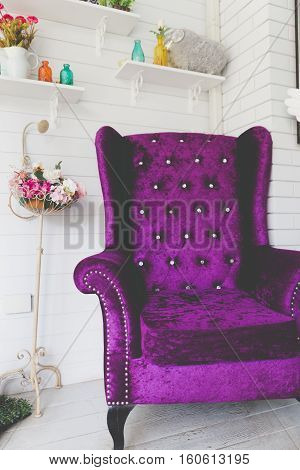 Old Style Retro Vintage Purple Velvet Armchair Beside White Wood Wall