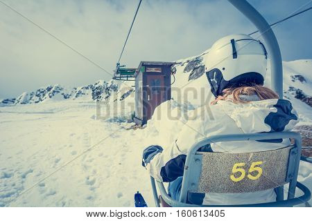 Back view of skier riding a lift. Skking in the mountains.