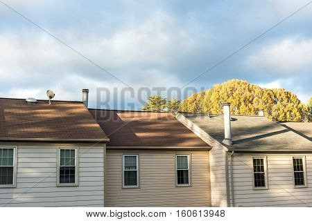 Row of three townhouses with stormy clouds and golden autumn tree