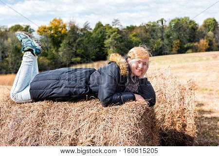 Young woman lying down on hay roll bale