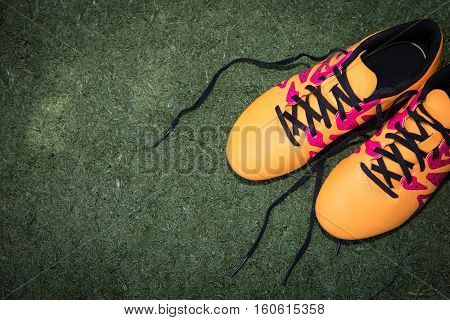 Yellow athletic junior shoes on a green plastic grass
