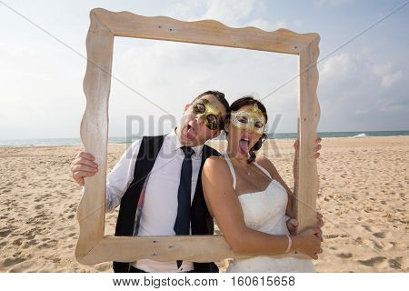 Fun Wedding Couple With Masque Venetian On The Beach Play With Photographer