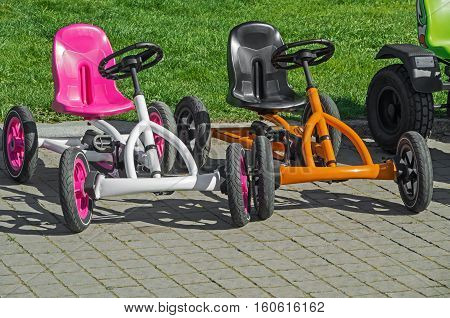 Two children's four-wheeled bicycles on pavement at the amusement park