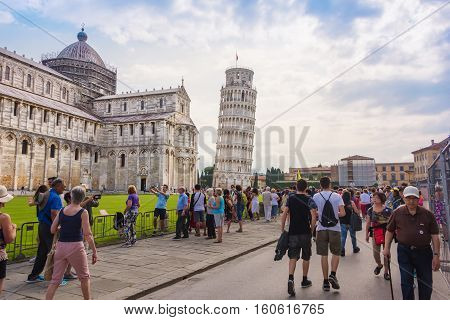 Pisa Italy - June 9 2016: Tourists gather in the Square of Miracles in Pisa to see the Leaning Tower of Pisa and the medieval cathedral of the Archdiocese of Pisa.