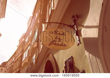 Sign on the wall that says made in Prague . Bright sunny picture of street in the old town of Prague, Czech Republic