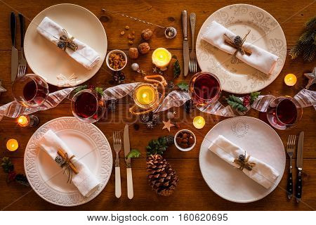 Christmas table setting for family dinner at a cosy rustic table with candles and decorations. Top view.