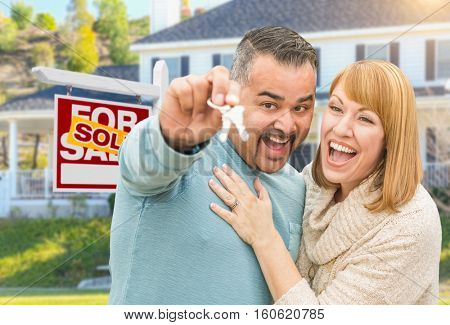 Happy Mixed Race Couple With Keys in Front of Sold For Sale Real Estate Sign and New House.