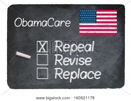 Obamacare health plan choice of Repeal written in chalk on a chalky natural slate blackboard isolated against white background