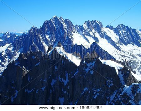 Alpine mountains range in beautiful French, Italian and Swiss Alps seen from Aiguille du Midi with clear blue sky in warm and sunny summer day, CHAMONIX MONT BLANC, EUROPE on JULY.