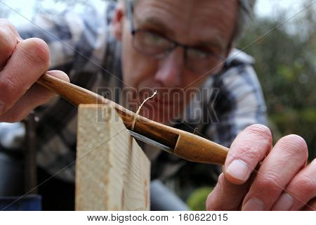 Traditional woodworker using antique boxwood spokeshave woodwork tool