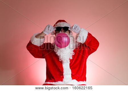 Santa with sun glasses blowing pink chewing gum peeking at the camera