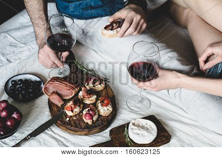 Couple eating dinner of italian cuisine with red wine and antipasto snacks set: bruschettas, crostini, prosciutto, camambert cheese, grapes and black olives. Selective focus, desaturated effect.