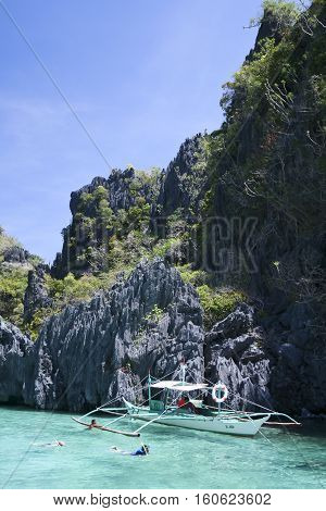 El Nido PhilippinesS - May 18 2007: tourists snorkel around banka tour boat in hidden karst lagoon. El Nido is one of the top tourist destinations in the world.