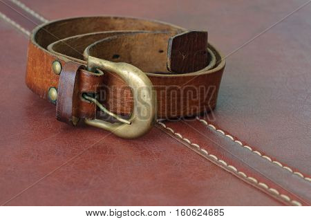 used leather belt for men on brown leather background