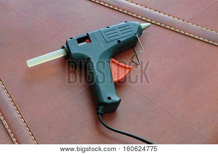 hot adhesive gun. Glue gun on a brown background