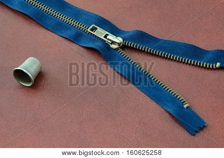 Blue zipper half unzipped and thimble brown leather background