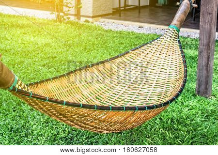 hanging bench seat chair cradle hammock in basket design on the green grass field