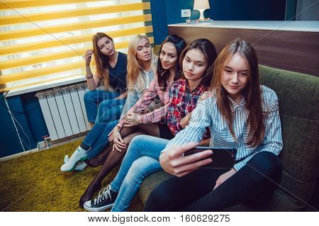 Beautiful girls sitting on the couch, have fun and make selfie in Hostel