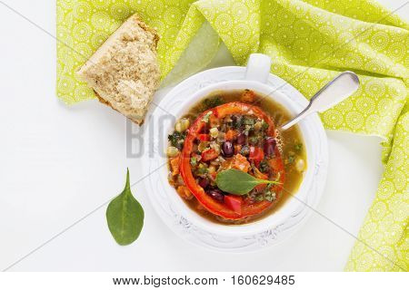 Spiced vegan kidney bean and lentil thick soup with tomatoes and bell pepper. Vintage ceramic bowl on white table top view.