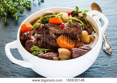 Beef Bourguignon in a white soup bowl on black stone background. Stew with carrots onions mushrooms bacon garlic and bouquet garni. The dish is served with fresh thyme.