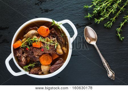 Beef Bourguignon in a white soup bowl on black stone background top view. Stew with carrots onions mushrooms bacon garlic and bouquet garni. The dish is served with fresh thyme.