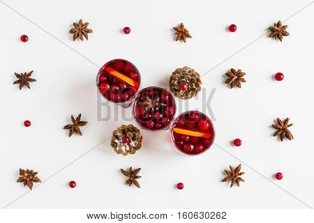 Mulled wine in small glasses with cranberries anise and oranges. White background top view.