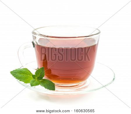 Isolated cup of black tea with mint leaves on white background. Transparent cup and saucer