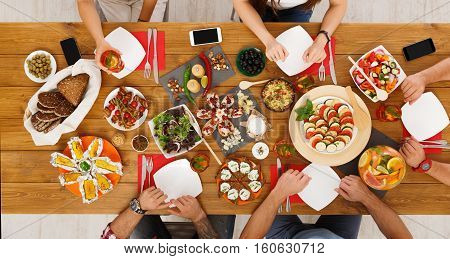 People eat healthy meals with non-alcoholic cocktails at festive table served for party. Friends celebrate with organic food on wooden table top view.