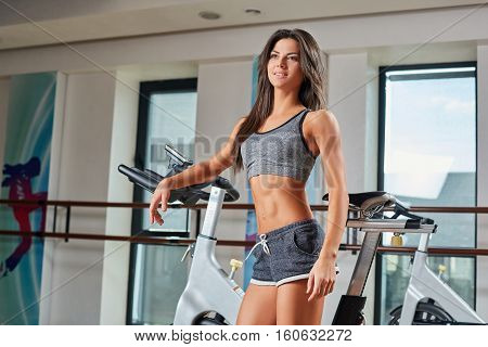 Sport young woman standing near a bike in the gym. She smiles and looks ahead