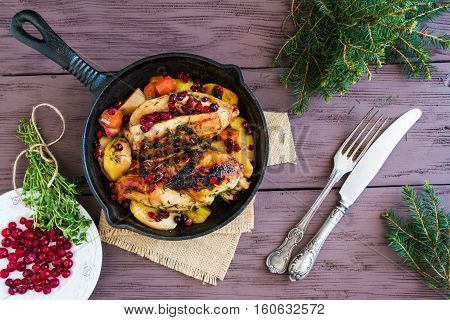 Baked chicken breast with carrots cranberries and potatoes. Marinated with thyme garlic and olive oil. Black cast-iron pan wooden table top view.